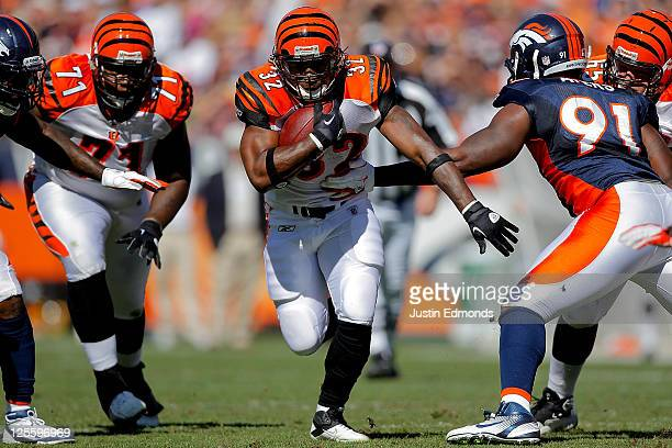 Running Back Cedric Benson of the Cincinnati Bengals runs with the ball past defensive end Robert Ayers of the Denver Broncos at Sports Authority...