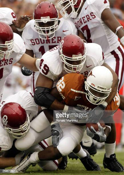 Running back Cedric Benson of the Texas Longhorns is tackled by Jonathan Jackson of the Oklahoma Sooners at the Cotton Bowl on October 11 2003 in...