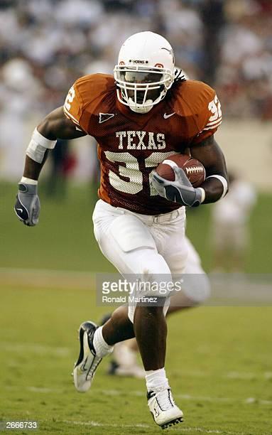 Running back Cedric Benson of the Texas Longhorns runs the ball against the Tulane Green Wave at Texas Memorial Stadium on September 27 2003 in...