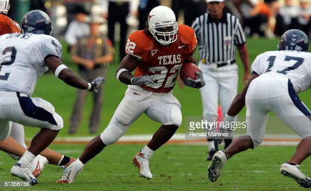 Running back Cedric Benson of the University of Texas Longhorns runs the ball past Andray Downs and Chad Price of the Rice Owls in the first quarter...