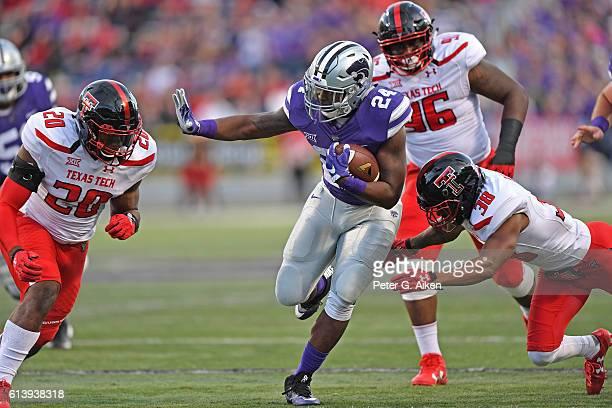 Running back Charles Jones of the Kansas State Wildcats rushes between defenders Paul Banks III and Jordyn Brooks of the Texas Tech Red Raiders...