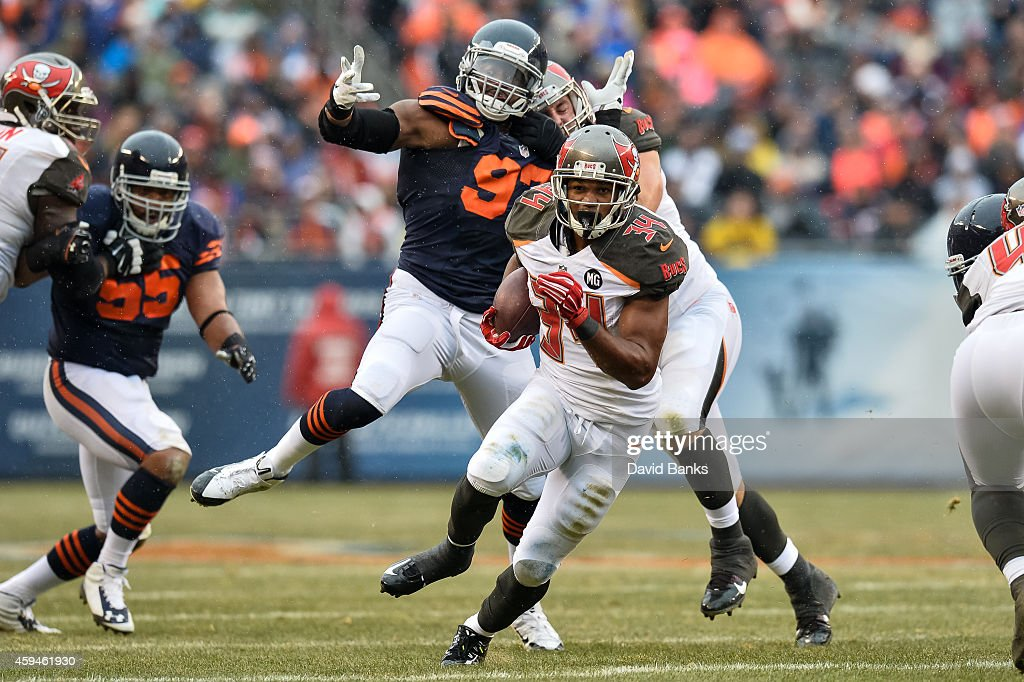 Running back Charles Sims #34 of the Tampa Bay Buccaneers carries the football past defensive end Willie Young #97 of the Chicago Bears in the first quarter at Soldier Field on November 23, 2014 in Chicago, Illinois.