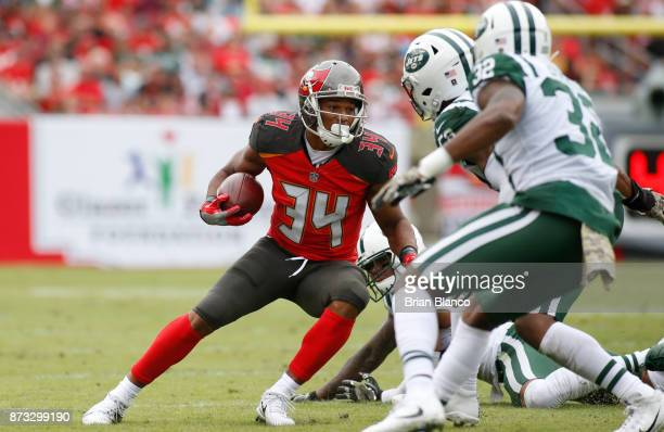 Running back Charles Sims of the Tampa Bay Buccaneers evades inside linebacker Demario Davis of the New York Jets and cornerback Juston Burris during...