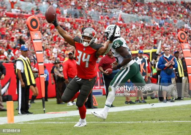 Running back Charles Sims of the Tampa Bay Buccaneers evades inside linebacker Demario Davis of the New York Jets as he runs into the end zone for a...