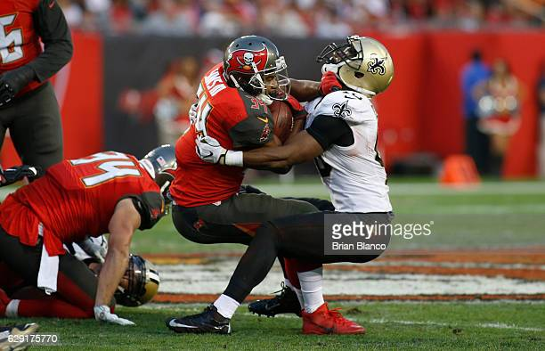 Running back Charles Sims of the Tampa Bay Buccaneers fends off cornerback Delvin Breaux of the New Orleans Saints during a carry in the second...