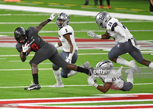 Running back Charles Williams of the UNLV Rebels is tackled by defensive back JoJuan Claiborne of the Nevada Wolf Pack as defensive back Emany...