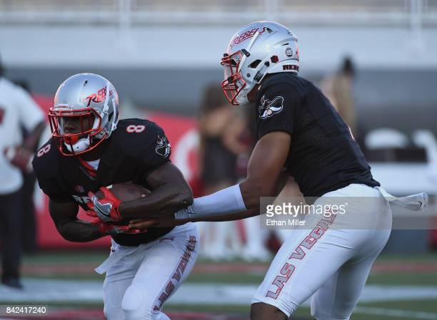 Running back Charles Williams of the UNLV Rebels takes a handoff from quarterback Armani Rogers as they warm up before a game against the Howard...