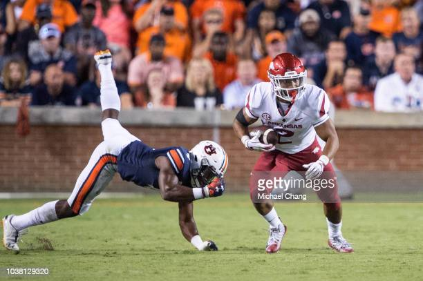 Running back Chase Hayden of the Arkansas Razorbacks runs the ball by defensive back Noah Igbinoghene of the Auburn Tigers during the second quarter...