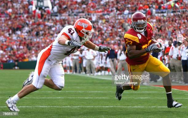 Running back Chauncey Washington of the USC Trojans runs to score touchdown over the defense of Jeremy Leman of the Illinois Fighting Illini in the...