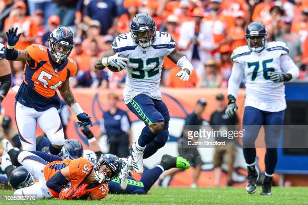 Running back Chris Carson of the Seattle Seahawks breaks a tackle attempt by defensive back Justin Simmons of the Denver Broncos at Broncos Stadium...