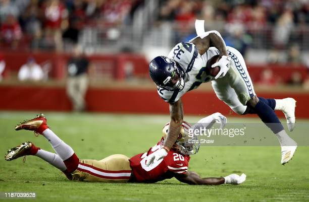 Running back Chris Carson of the Seattle Seahawks carries the ball against the defense of free safety Jimmie Ward of the San Francisco 49ers in the...