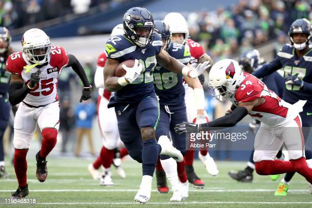 Running back Chris Carson of the Seattle Seahawks carries the ball against the defense of strong safety Jalen Thompson of the Arizona Cardinals...