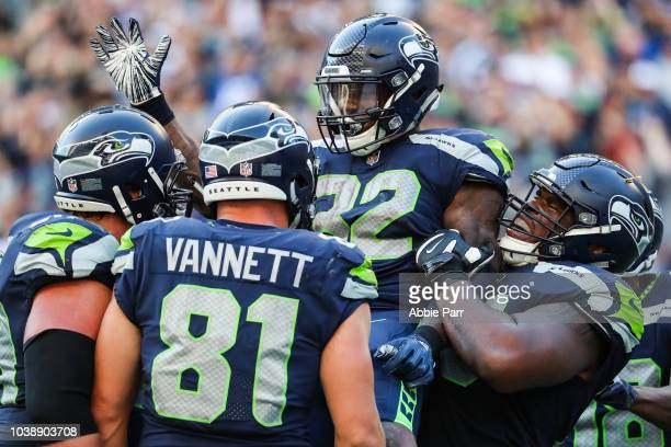 Running Back Chris Carson of the Seattle Seahawks celebrates with teammates after a second half touchdown against the Dallas Cowboys at CenturyLink...