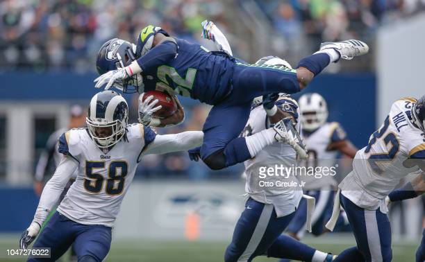 Running back Chris Carson of the Seattle Seahawks is tackled by linebacker Cory Littleton and defensive tackle Michael Brockers of the Los Angeles...