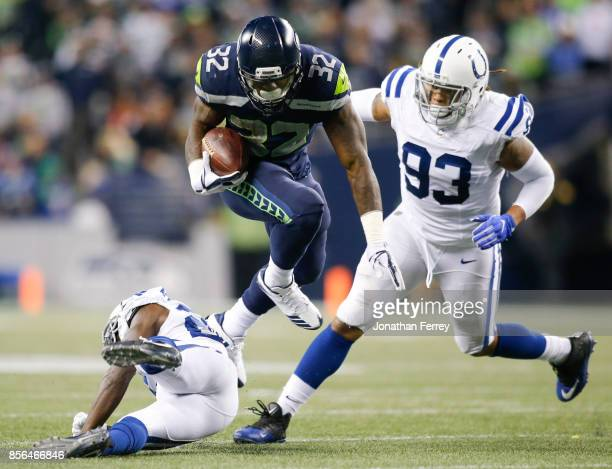 Running back Chris Carson of the Seattle Seahawks jump over Nate Hairston of the Indianapolis Colts while being pursued by Jabaal Sheard in the third...