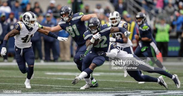 Running back Chris Carson of the Seattle Seahawks runs with the ball as linebacker Cory Littleton of the Los Angeles Rams tries to make a tackle and...