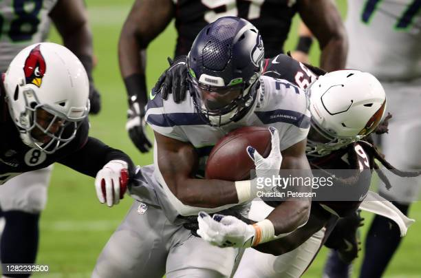 Running back Chris Carson of the Seattle Seahawks runs with the ball after a catch while being tackled by linebacker De'Vondre Campbell of the...