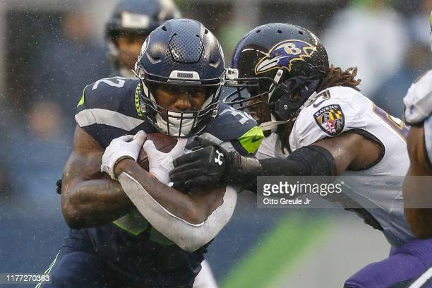 Running back Chris Carson of the Seattle Seahawks rushes against linebacker Josh Bynes of the Baltimore Ravens at CenturyLink Field on October 20,...