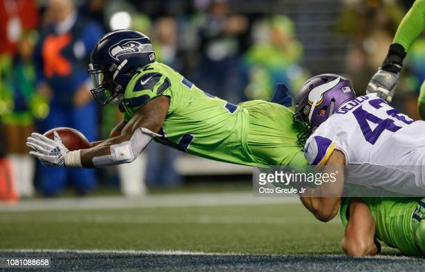 Running back Chris Carson of the Seattle Seahawks scores a touchdown against Ben Gedeon of the Minnesota Vikings in the fourth quarter at CenturyLink...