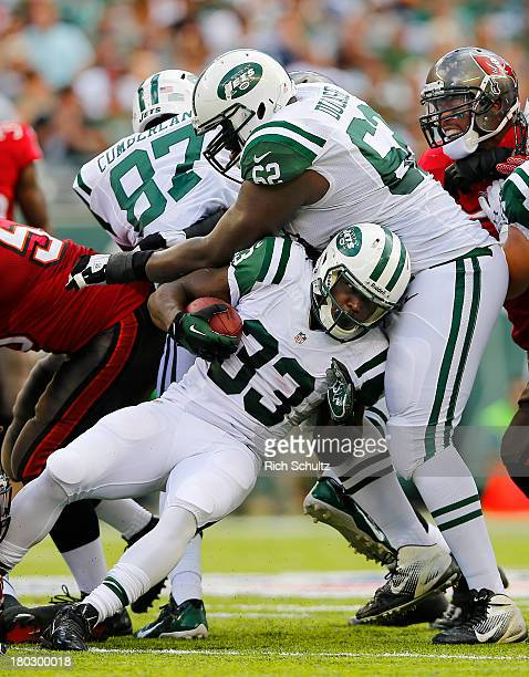 Running back Chris Ivory of the New York Jets runs for a first down and into his teammate guard Vladimir Ducasse against the Tampa Bay Buccaneers...