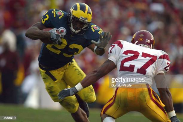 Running back Chris Perry of the Michigan Wolverines attempts to evade safety Jason Leach of the USC Trojans during the 2004 Rose Bowl game on January...