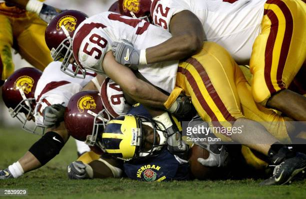 Running back Chris Perry of the Michigan Wolverines is buried under the defense of the USC Trojans during the 2004 Rose Bowl on January 1 2004 at the...