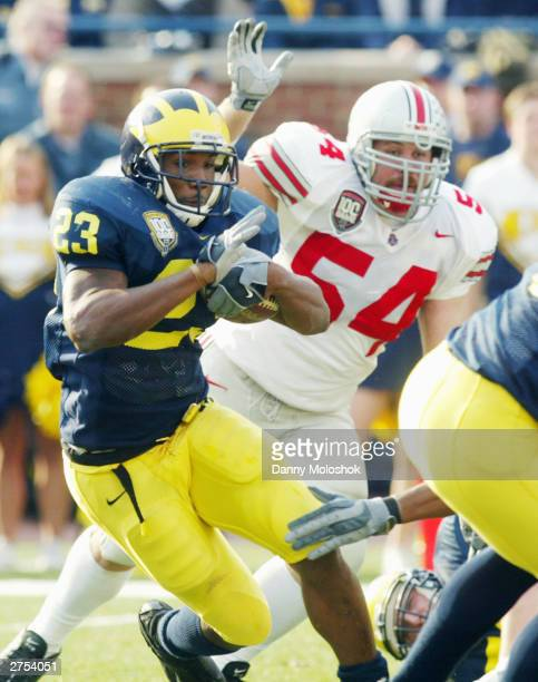 Running Back Chris Perry of the Michigan Wolverines runs the ball past Tim Anderson of the Ohio State Buckeyes during his team's 3521 win during the...