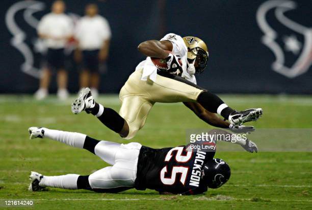 Running back Chris Taylor of the New Orleans Saints is tripped up by cornerback Kareem Jackson of the Houston Texans at Reliant Stadium on August 20,...