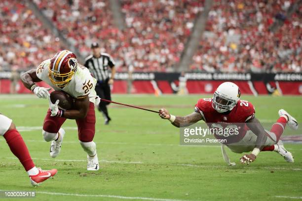 Running back Chris Thompson of the Washington Redskins carries the football as linebacker Deone Bucannon of the Arizona Cardinals attempts a tackle...
