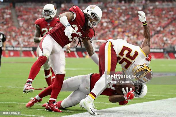 Running back Chris Thompson of the Washington Redskins is tackled by defensive back Tre Boston and defensive back Jamar Taylor of the Arizona...
