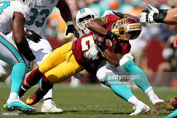 Running back Chris Thompson of the Washington Redskins is tackled by outside linebacker Koa Misi of the Miami Dolphins in the first half of a game at...