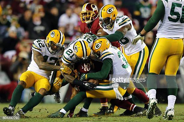 Running back Chris Thompson of the Washington Redskins is tackled by free safety Ha Ha Clinton-Dix and strong safety Micah Hyde of the Green Bay...