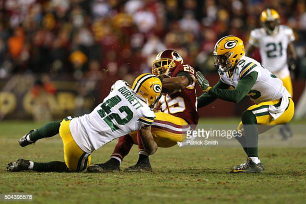 Running back Chris Thompson of the Washington Redskins is tackled by strong safety Morgan Burnett and strong safety Micah Hyde of the Green Bay...