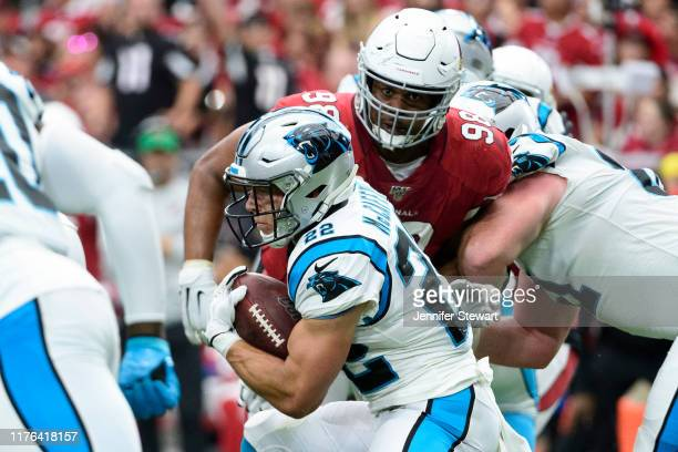 Running back Christian McCaffrey of the Carolina Panthers carries the ball in front of defensive tackle Corey Peters of the Arizona Cardinals in the...