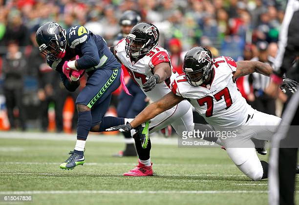 Running back Christine Michael of the Seattle Seahawks rushes against defensive tackle Grady Jarrett and defensive tackle Ra'Shede Hageman of the the...