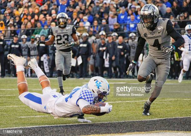Running back Christopher Rodriguez Jr #24 of the Kentucky Wildcats dives past defensive back Randall Haynie of the Vanderbilt Commodores to score a...