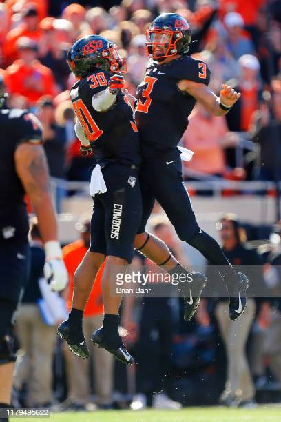 Running back Chuba Hubbard and quarterback Spencer Sanders of the Oklahoma State Cowboys celebrate a touchdown against the TCU Horned Frogs in the...
