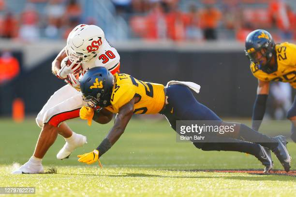 Running back Chuba Hubbard of the Oklahoma State Cowboys gets hit by safety Tykee Smith of the West Virginia Mountaineers in the fourth quarter on...