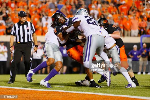 Running back Chuba Hubbard of the Oklahoma State Cowboys pushes his way into the end zone against linebacker Daniel Green and defensive back Denzel...