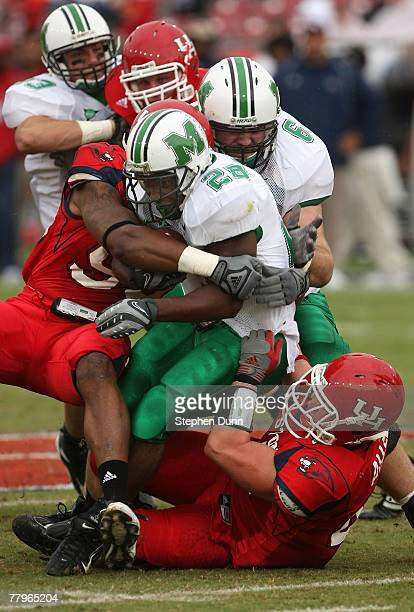 Running back Chubb Small of the Marshall Thundering Herd is tackled by defensive lineman Ell Ash and linebacker Trent Allen of the Houston Cougars at...