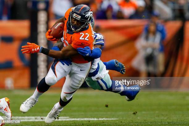 Running back CJ Anderson of the Denver Broncos avoids a tackle attempt by outside linebacker Jaylon Smith of the Dallas Cowboys in the first half of...