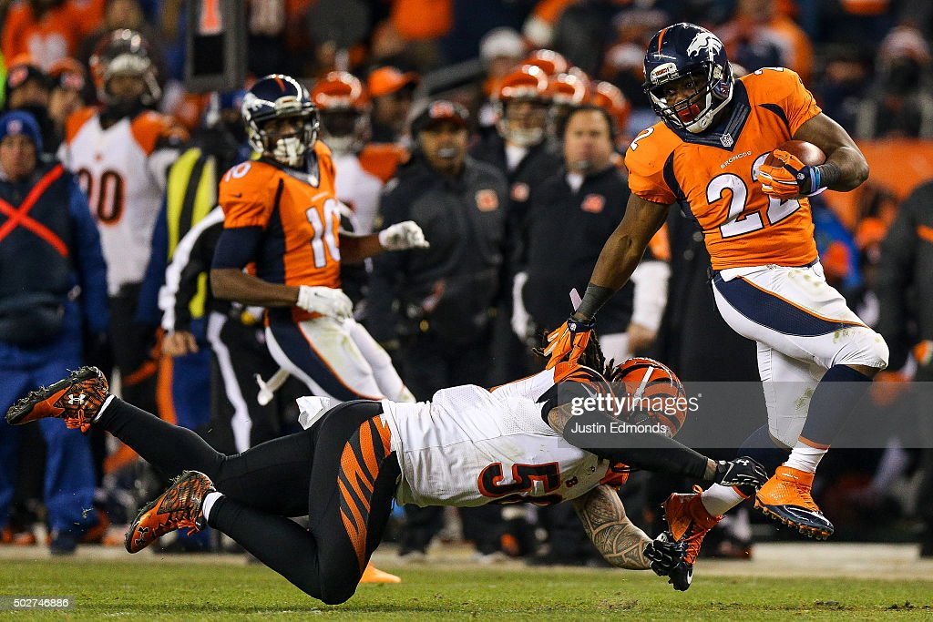 Running back C.J. Anderson #22 of the Denver Broncos breaks away from a tackle attempt by middle linebacker Rey Maualuga #58 of the Cincinnati Bengals as he rushes for a 39 yard fourth quarter go-ahead touchdown during a game at Sports Authority Field at Mile High on December 28, 2015 in Denver, Colorado..