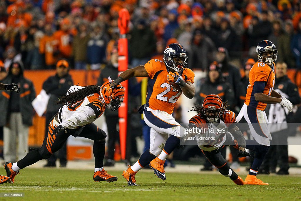 Running back C.J. Anderson #22 of the Denver Broncos breaks away from tackle attempts by free safety Reggie Nelson #20 and cornerback Adam Jones #24 of the Cincinnati Bengals as he rushes for a 39 yard fourth quarter go-ahead touchdown during a game at Sports Authority Field at Mile High on December 28, 2015 in Denver, Colorado..