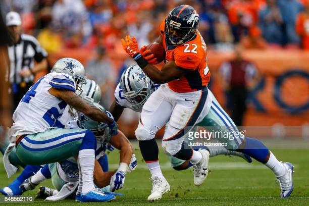 Running back CJ Anderson of the Denver Broncos escapes from a group of Dallas Cowboys defenders in the first half of a game at Sports Authority Field...