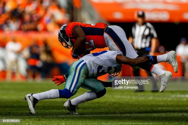 Running back CJ Anderson of the Denver Broncos is hit by cornerback Anthony Brown of the Dallas Cowboys after picking up a second quarter first down...