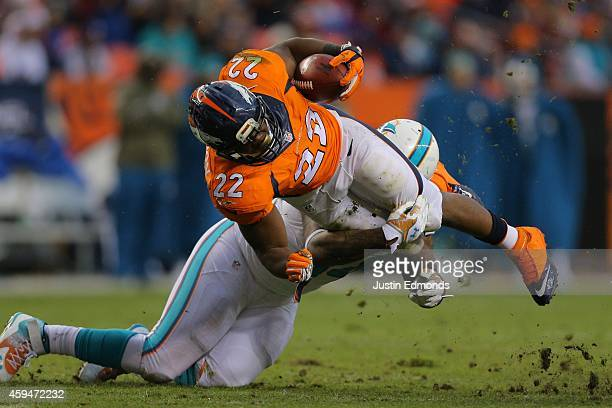 Running back C.J. Anderson of the Denver Broncos is tackled by defensive tackle Randy Starks of the Miami Dolphins during a game at Sports Authority...