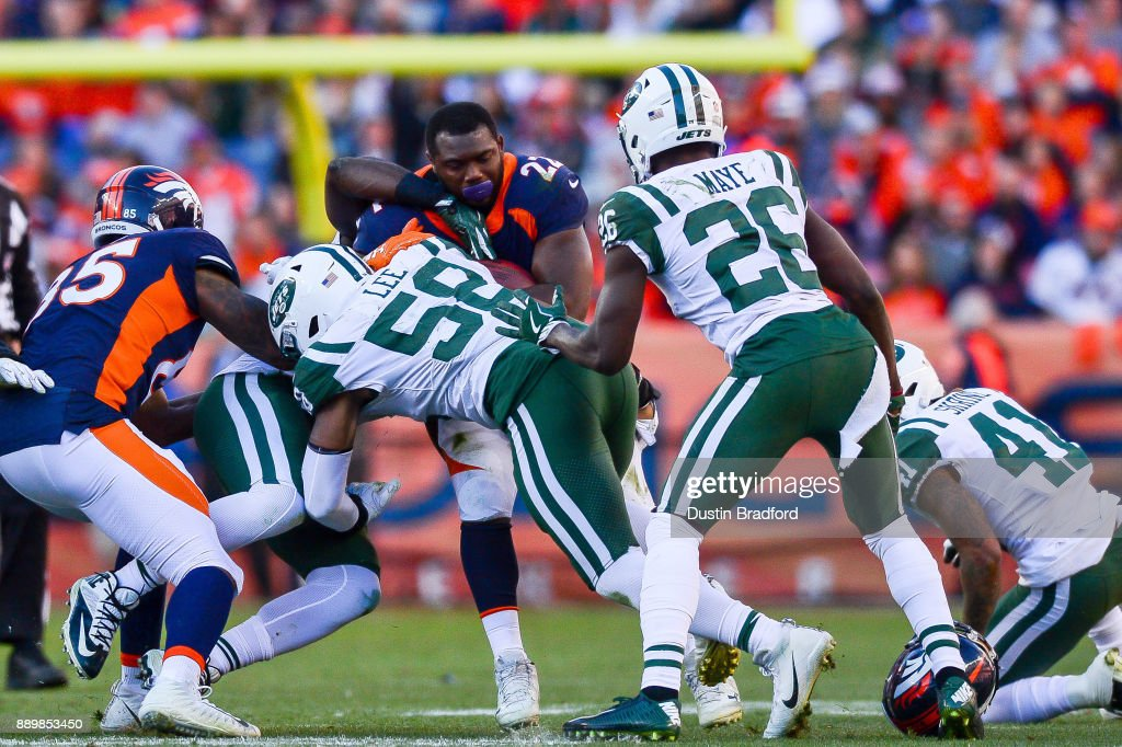 Running back C.J. Anderson #22 of the Denver Broncos loses his helmet as he is hit by inside linebacker Darron Lee #58 of the New York Jets during a game at Sports Authority Field at Mile High on December 10, 2017 in Denver, Colorado.