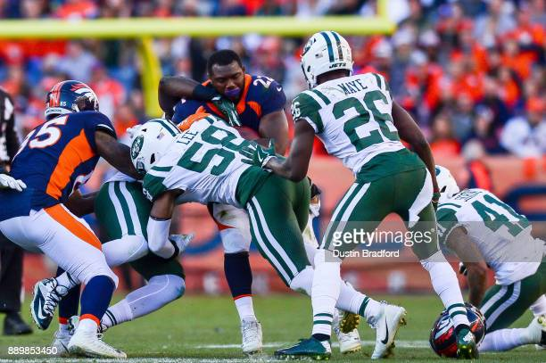 Running back CJ Anderson of the Denver Broncos loses his helmet as he is hit by inside linebacker Darron Lee of the New York Jets during a game at...