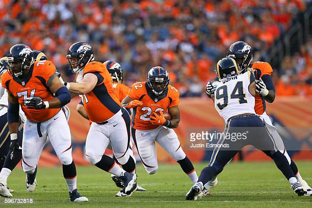 Running back CJ Anderson of the Denver Broncos runs through a hole during the first quarter against the Los Angeles Rams at Sports Authority Field at...