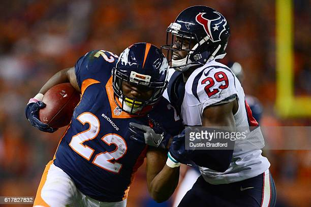 Running back CJ Anderson of the Denver Broncos rushes for 19 yards and is tackled by free safety Andre Hal of the Houston Texans in the third quarter...